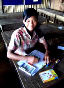 One of the older students does her homework at Iqbal school. Female older student enrollment at government school in Cambodia is very low.