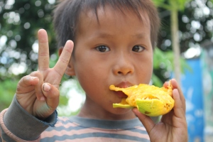 One of our students tucks into a vitamin-A rich mango from our trees on site.